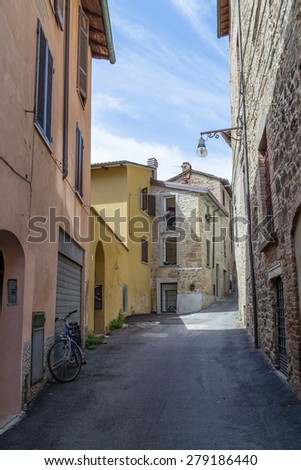 Old houses facing each other in a street in the old town of a country town in Italian countryside