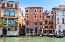 Old houses on Grand Canal, Venice, Italy. Vintage hotels and residential buildings in the Venice center. Historical architecture of Venice on water in summer. Venetian street with ancient facades.