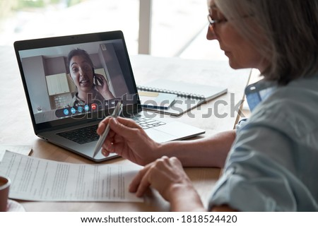 Old hr employer checking indian female job applicant cv resume by video conference call interview on laptop. Senior client reading insurance contract with virtual lawyer advisor at online legal advice