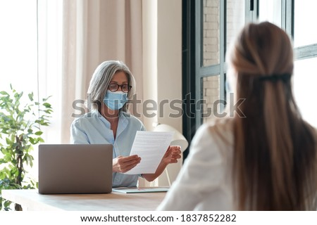 Old hr manager checking female job applicant cv resume at job interview meeting. Senior employer wearing face mask reading seeker employment application. Social distance and safety at work concept.
