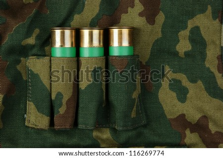 Old hunting cartridges and bandoleer on camouflage background