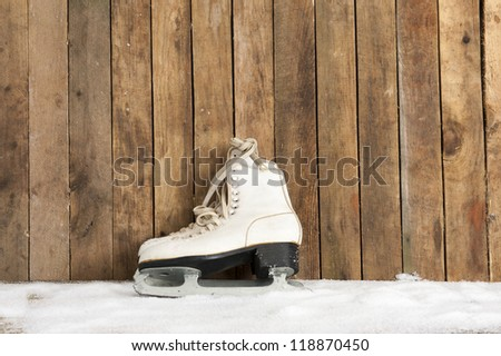 old ice skates against an weathered wooden wall