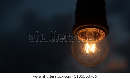 Old incandescent light bulb hanging on cloudy sky at night background, Thinking and idea concept, Innovation Symbol, widescreen background 16:9