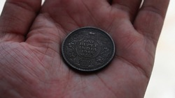 Old Indian One Rupee coin 1918 or Currency Photo Close up in hand ( Written One Rupee India 1918 on it )