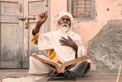 Old indian sadhu (saint) sitting and speak up sacred texts near the temple.