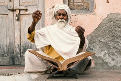 Old indian sadhu (saint) sitting and speak up sacred texts with closed eyes near the temple.