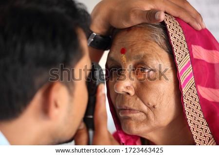 Old Indian woman in pink mantilla from Rajasthan getting eyes tested. Eye camp. Eye patient. Weak eyesight. Eye Health. Eye examination by doctor. Healthcare to elderly.