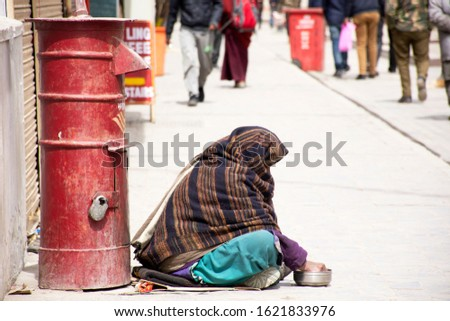 Old indian women beggar or untouchables caste sit and begging money from travelers people in market at Leh Ladakh Village in Jammu Kashmir, India
