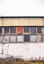 Old industrial building with broken windows and rusted metal wall with old fan. Air conditioner. Cooling.