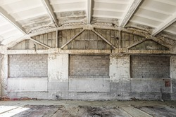Old industrial building with wet, mold damaged reinforced concrete building structures of workshop