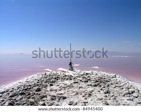 Old industrial equipment along the salty shore of the great Salt Lake in Utah with mountains in the background. The water looks pink due to a special algae that grows in high levels of salt.