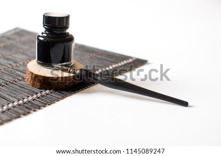 Old ink pen and ink bottle isolated on white background. Vintage calligraphy pen and bottle of ink. Selective focus. Close up.