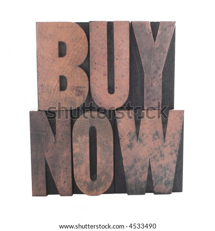 old, inkstained wood letterpress type spells out the words 'buy now' in all caps