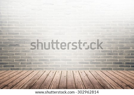 Old interior room with broken dark brick wall and grunge brown wooden floor texture with light on top