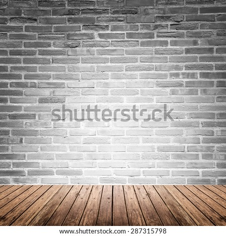 Old interior room with broken gray brick wall and grunge wood floor texture