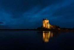 Old Irish Dunguaire Castle by the water at night with reflection