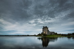 Old Irish Dunguaire Castle near the water in the evening with reflection