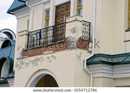 Old iron balcony on a gray building #1054712786