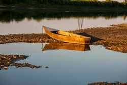 Old iron boat on the river bank, the bow of the boat is in the sand, and the stern is in the water at sunset