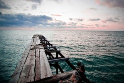 Old iron bridge with wooden boards in the winter sea against the sunset sky with clouds