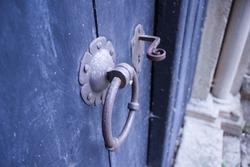 Old iron door knocker and door handle on a medieval church's side door