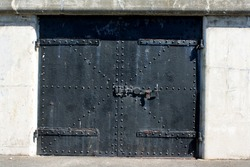 Old iron door reinforced with steel belts and rivets guarding the entrance to an old military fort.