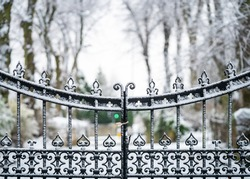 Old iron gates with victorian ironwork locked closed with snowy scene falling and heavy snow settling on metal.  Line of trees in winter landscape entrance driveway.
