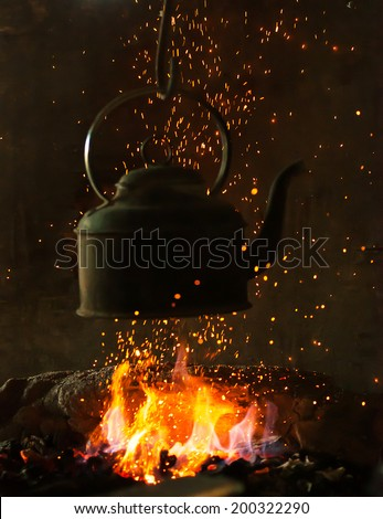 Old iron kettle on the fire, sparks fire
