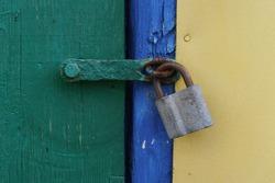 old iron lock on a green wooden door, closed door.