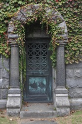 Old Iron Metal Doors Overgrown with Ivy on a Mausoleum in a Cemetery