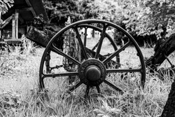 old iron wagon wheel abandoned in the grass