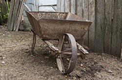 Old iron wheelbarrow. Rusty garden cart