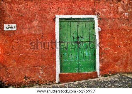 Old Italian red wall with green wooden door