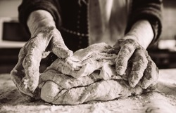 old italian woman making pasta in the kitchen sepia effect