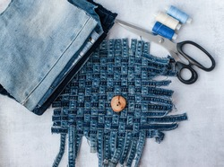 Old jeans ready to upcycling, thread, scissors and pattern, made from old jeans pieces. Concept of things reuse and natural resources preserving.