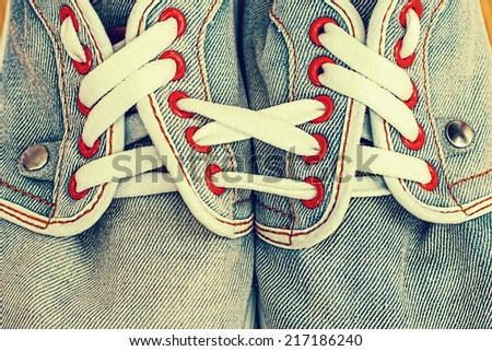 Old jeans sports shoes laced unusually #217186240