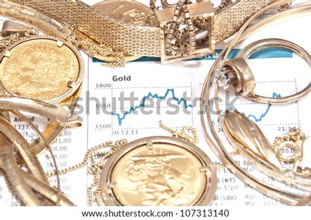 Old jewelry and gold coins with printed gold chart in background