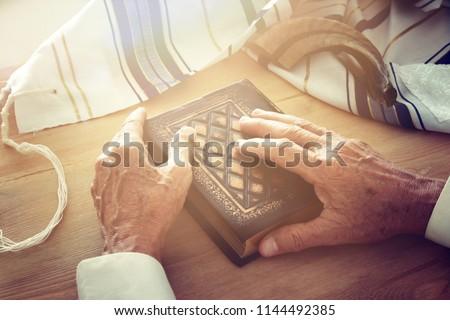 Old Jewish man hands holding a Prayer book, praying, next to tallit and shofar (horn). Jewish traditional symbols. Rosh hashanah (jewish New Year holiday) and Yom kippur concept Stockfoto ©
