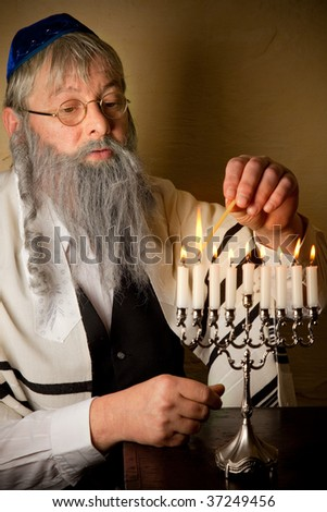 Old jewish man lighting candles of a hannukah menorah