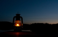 Old kerosene lantern with warm yellow light on a bridge by a lake in the evening.