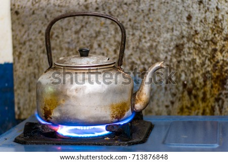 Old kettle on flame while boil water
