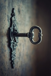 Old key in keyhole, macro shot. Gothic style. Key to knowledge. Concept and Idea for History, education, business, security, secret background.