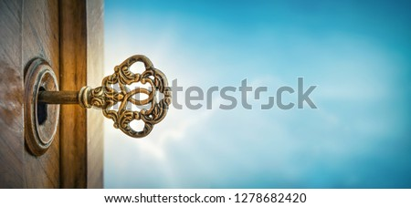 Old key in keyhole on sky background with sun ray . Concept, symbol and Idea for History, business, security, religion background. stock photo