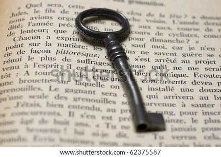 Old key on a open book
