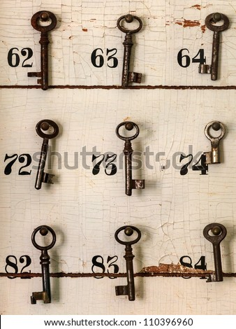Old keys with numbers hanging on a weathered wall of an old hotel