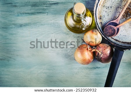 Old kitchen pan wooden spoon three onions carafe with olive oil on wooden table. Some of the equipment of the old kitchen in retro style