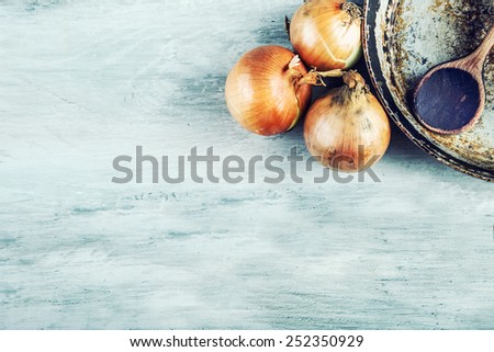 Old kitchen pan wooden spoon three onions on wooden table. Some of the equipment of the old kitchen in retro style
