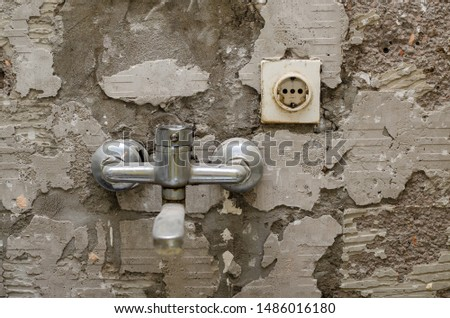 Old kitchen tap and a socket on a scraped wall during reconstruction works