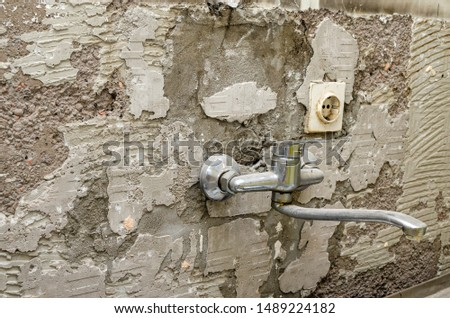 Old kitchen tap on an a wall during reconstruction works