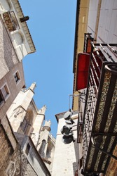 old kitchen utensils hanging on the facade for advertising,Photographs in angle against chopped streets and facades of Toledo, Spain, narrow street, windows and balconies with wrought iron grills, art
